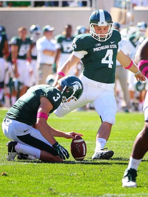 Michigan State Spartans kicker Michael Geiger (4) attempts to kick out of the hold by punter Mike Sadler (3) during the first half in a game at Spartan Stadium.