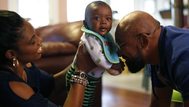 Lorraine and Charles Nichols play with their son Caleb Charlie Nichols, seven mo., in their living room Dec 12. Lorraine first laid eyes on the baby when she cared for him at TMH where he was brought after being discovered in the back of a pickup truck. Four days later she took him home to join her family.