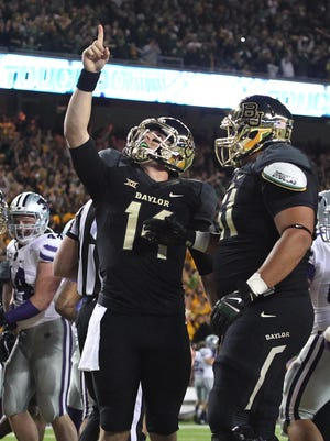 Baylor quarterback Bryce Petty (14) points upward with teammate Jarell Broxton following his touchdown against Kansas State Saturday. Baylor had hoped to be part of the college football playoff. Instead, ranked fifth, the Bears will play MSU in the Cotton Bowl on Jan. 1.