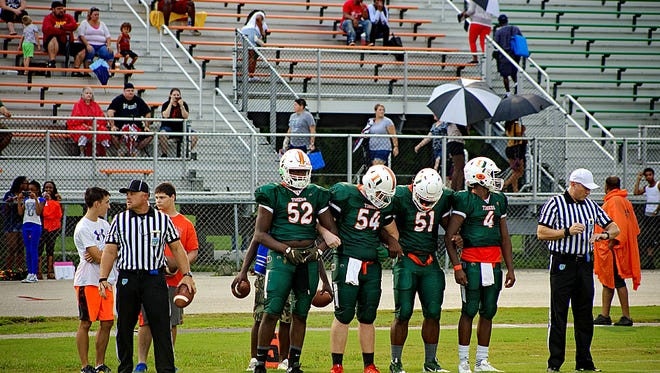 Dunbar players (from left) Derick Hunter, Luke Ford, Judas McKenzie and  Zacharie Georges line up for the pregame coin flip before the Tigers took on Charlotte High Saturday night. Dunbar won 33-14 to snap the Tarpons' 22-game regular-season win streak..