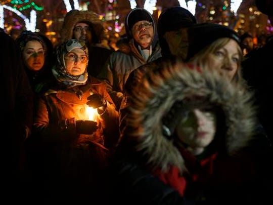 People gather in remembrance of the victims of Sunday's shooting at a Quebec City mosque, during a vigil in Edmonton, Alberta, Monday, Jan. 30, 2017. A French Canadian known for far-right, nationalist views was charged Monday with six counts of first-degree murder and five counts of attempted murder over the shooting rampage at a Quebec City mosque that Canada's prime minister called an act of terrorism against Muslims.