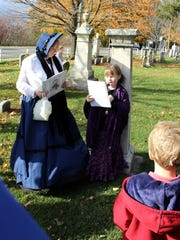 Vicki Masters Profitt holds the microphone as her daughter Alison – portraying 4-year old Lilly Osgoodby – tells of the scarlet fever epidemic which struck Pittsford in 1868.