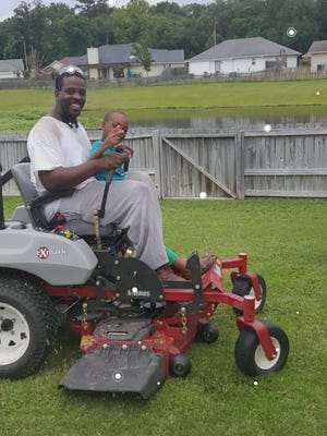 Lorenzo Parker and his son are shown with one of the pieces of equipment that was stolen from a storage unit, which impacted Parker's side business of mowing lawns.