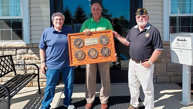 Gordon Conrad, U.S. Army, Ralph Tomassi, HNCO, and Dave Bowser, U.S. Marines post with a plaque honoring veterans.