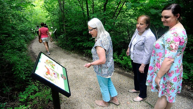 Mansfield Richland County Public Library outreach librarian Anne Rhodes and outreach coordinator Deborah Dubois along with Stephanie Blanchard from Park National Bank check out one of the pages on Kingwood Center's Storybook Trail Friday.
