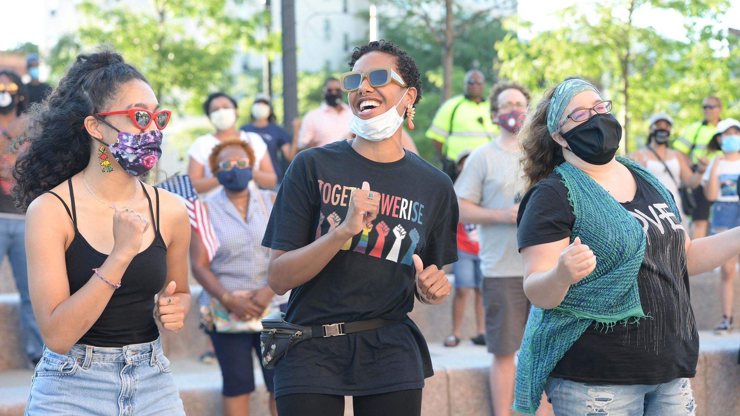 Women celebrate Juneteenth outside a city hall.