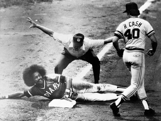 FILE - In this Sept. 10, 1974, file photo, Cleveland Indians' Oscar Gamble flashes a smile after sliding safely into third in the sixth inning of baseball game against the Detroit Tigers in Cleveland, Ohio, Sept. 10, 1974. Gamble doubled and made it to third on an outfield error. Detroit's Ron Cash watches as umpire Bill Kunkel flashes the safe signal. Gamble, an outfielder who hit 200 home runs over 17 major league seasons, died Wednesday, Jan. 31, 2018, of a rare tumor of the jaw. He was 68. (AP Photo/File)