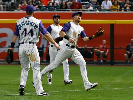 Arizona Diamondbacks' Brandon Drury, right, makes the catch on a foul ball hit down the line by Pittsburgh Pirates' Gerrit Cole as Paul Goldschmidt (44) and David Peralta, middle, watch during the sixth inning of a baseball game Thursday, May 11, 2017, in Phoenix. (AP Photo/Ross D. Franklin)