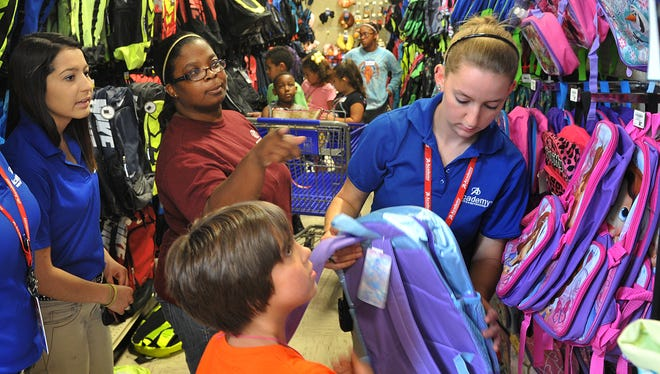 Staff members at the Boys and Girls Club in Wichita Falls, Texas pick out new backpacks for back to school. The Texas Sales Tax Holiday is this weekend and has become a popular event for families shopping for back to school supplies.