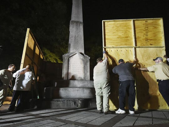 Birmingham city workers use plywood panels to cover the Confederate Monument in Linn Park, in Birmingham, Ala., Tuesday night, Aug. 15, 2017, on orders from Mayor William Bell.