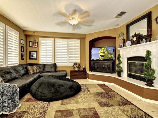The family room features a cozy fireplace, television niche, large windows with plantation shutters and surround sound.