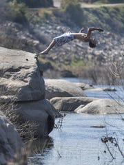 "Micheal Case of Visalia leaps from a rock into the Kaweah River near Slick Rock on Tuesday, March 14, 2017. He said the water was a ""little chilly."""