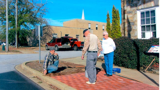 Shown are Sandra Denny observing Patriots Hall members, Jon Busch and Charles Brickett adding to Walk of Honor in front of the Veteran's Museum in Walhalla.