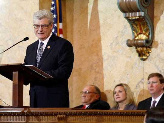 Gov. Phil Bryant outlines his legislative priorities as Lt. Gov. Tate Reeves, right, his wife Elee, center, and the President Pro Tempore Terry Burton, R-Newton, listen, during the State of the State address, Tuesday, Jan. 9, 2018, in House Chambers at the Capitol in Jackson, Miss.