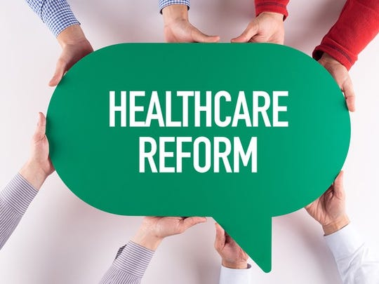 "Hands holding cut-out caption with ""healthcare reform"" printed on it"