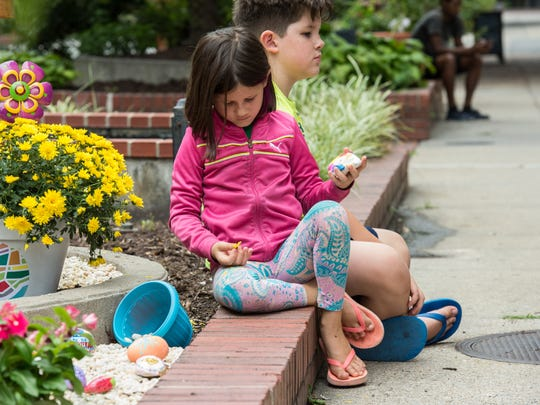 A young girl holds her Kindness rock just before the opening of Salisbury's Kindness Rocks garden on Monday, Aug. 14, 2017.