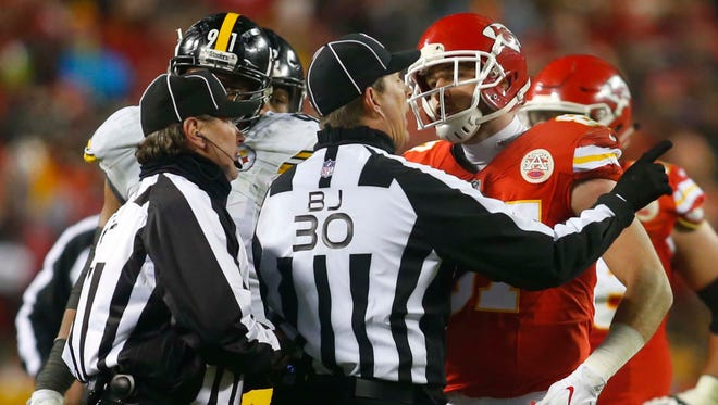 Kansas City Chiefs tight end Travis Kelce (87) is held back by back judge Todd Prukop (30) as he speaks to field judge Doug Rosenbaum (67) during the third quarter against the Pittsburgh Steelers in the AFC Divisional playoff game at Arrowhead Stadium.