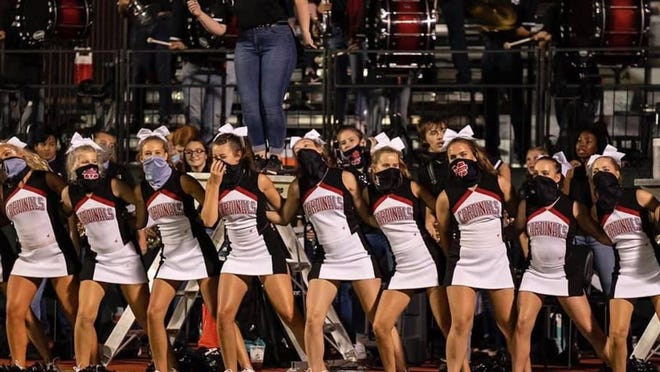 Melissa High School cheerleaders don face masks while performing during a recent varsity football game.