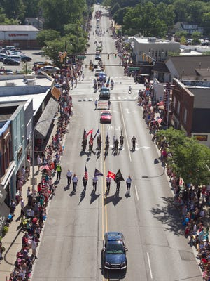 Provided a spectacular view from Brighton Area Fire's ladder 31, the Brighton Fourth of July Parade can be seen, led by the Color Guard, crosses Grand River as it proceeds down Main Street.