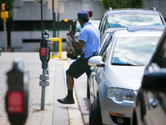 A parking enforcement officer checks the meters along North French Street in Wilmington.
