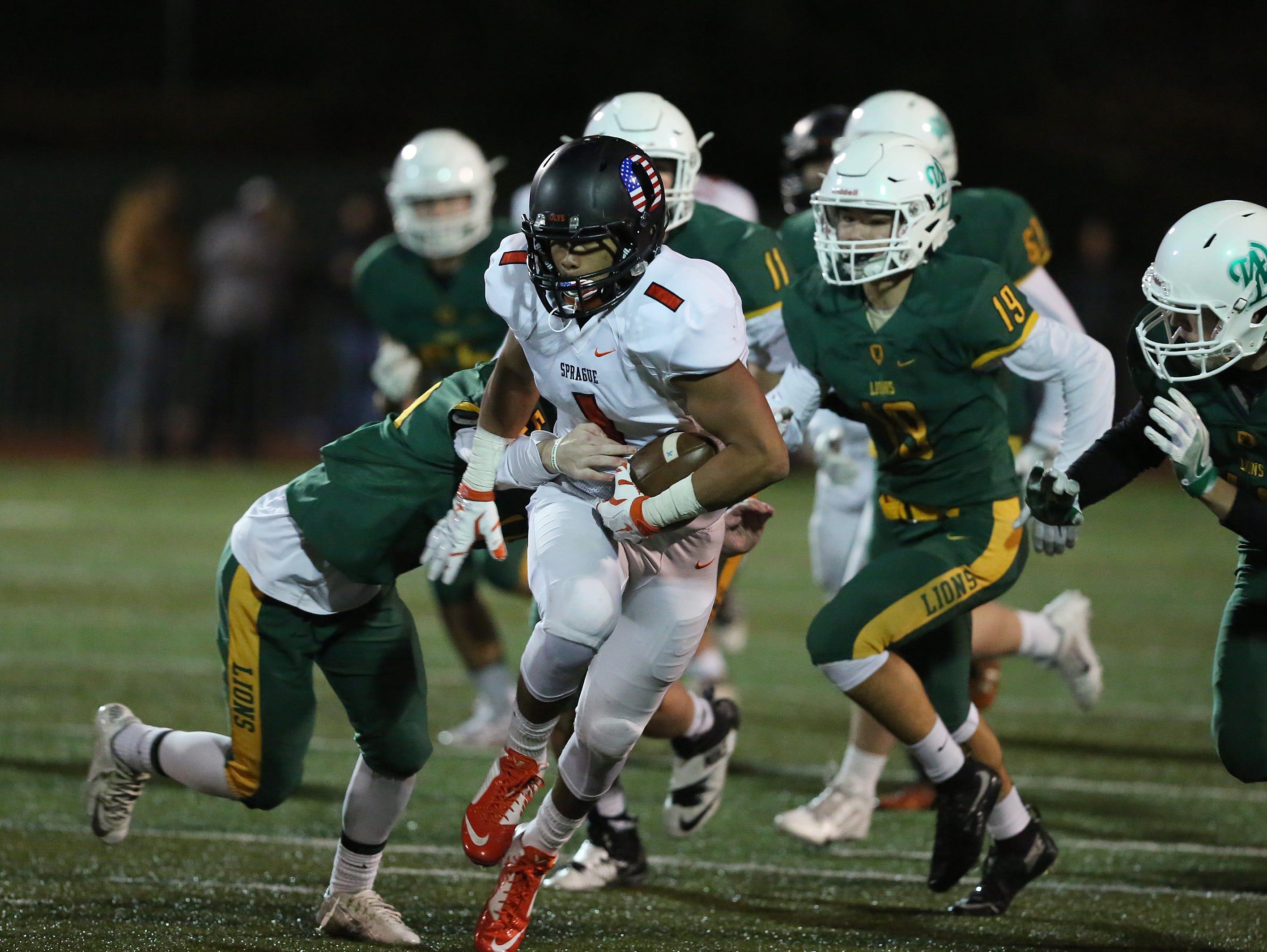 West Linn defenders try to take down Sprague's Noah Mellen in the OSAA Class 6A state quarterfinals on Friday, Nov. 18, 2016, at West Linn High School. West Linn defeated Sprague 56-20.
