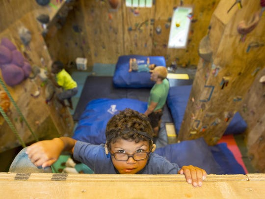 """Manny Eichhorn, 6, does some climbing in the rock climbing addition his dad, Gregg, built behind their home in Price Hill. Eichhorn, 30, and his wife, Katie, 29, have eight adopted children (one is pending). Seven have special needs. The couple met as teenagers and married when they were 19 and 18. He said, """"You have to be intentional about being a father. Having kids is a blessing, a joy."""" It said it also helps he thinks of himself as a big kid."""