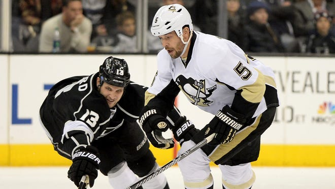 Jan 30, 2014; Los Angeles, CA, USA; Los Angeles Kings left wing Kyle Clifford (13) battles for the puck with Pittsburgh Penguins defenseman Deryk Engelland (5)  at Staples Center. The Penguins won 4-1.