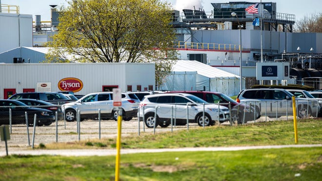 Vehicles are seen in the parking lot on the first day after a temporary shutdown due to an outbreak of COVID-19 April 21 at a Tyson Foods pork processing plant in Columbus Junction.
