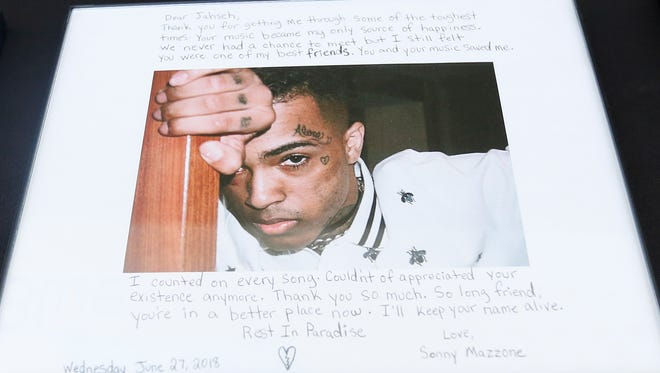 A fan leaves a letter for slain rapper, XXXTentacion, during a memorial on Wednesday, in Sunrise, Fla. The rapper was born Jahseh Dwayne Onfroy.