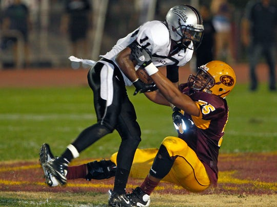 Chandler Hamilton's Cole Luke is tackled by Phoenix Mountain Pointe's Kyle Spight after Luke's interception  during the first half of their game on Friday, August 24, 2012 in Phoenix.