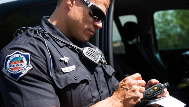Mesa police officer Jamie Bernau writes a ticket for a driver he pulled over in Mesa. Revenue from traffic tickets made up roughly 1.3 percent of Mesa's budget in fiscal year 2014.