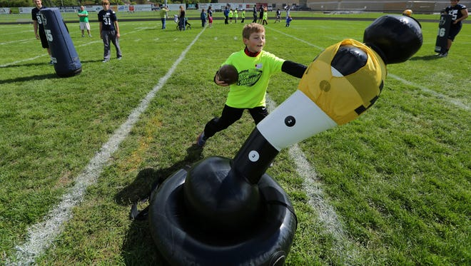 Sam Shopbell of Neenah carries the ball during a drill at a special football camp for children with autism. The event, held Sept. 12 at Xavier High School, was organized by the Autism Society of the Fox Valley and the Appleton Xavier football team.