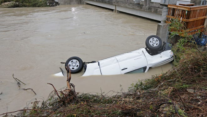 A pickup rests against the side of Gills Creek near a bridge in Columbia, S.C., Monday. Days of torrential rains kept much of South Carolina and its capital gripped by floodwaters early Monday.