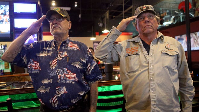 Arlen Pruett (left) and Mark Gurgevich salute during the National Anthem as Donald Trump becomes the 45th President of the United States during his inauguration Friday, Jan. 20, 2017, at Hard Knocks Sports Bar in Corpus Christi, Texas.