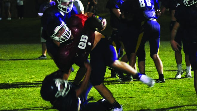 Randon Ray fights off a tackle attempt during the first full contact practice shortly after midnight Saturday.