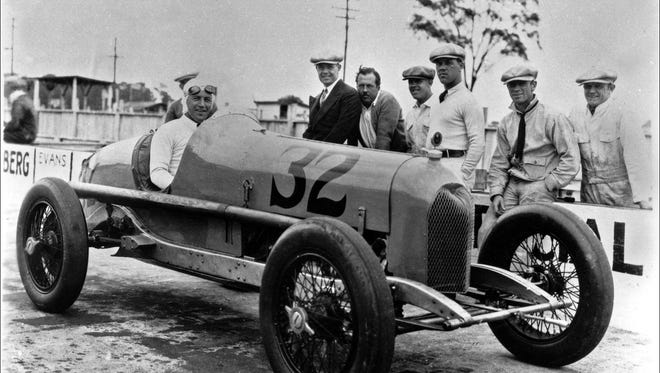Indianapolis Motor Speedway 1927 race winner GEORGE SOUDERS seated in the #32 Duesenberg Special. Crew and officials (behind car on pit wall) are uinidentified. Souders started 22nd.