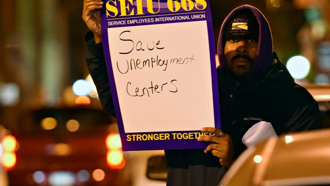 SEIU Local 668 staff member Christopher Hundley, of Springettsbury Township, rallies with furloughed state employees and other representatives outside of Senator Scott Wagner's office in York City, Monday, Dec. 19, 2016. More than 500 labor department workers were affected by the furlough, due to lack of funding. Dawn J. Sagert photo