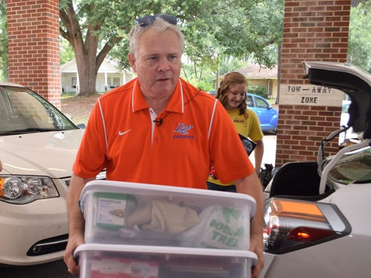 Louisiana College president Dr. Rick Brewer (left) helps students, like Lauren Dalme (back, right), move items into Cottingham Hall on the Louisiana College campus Saturday.