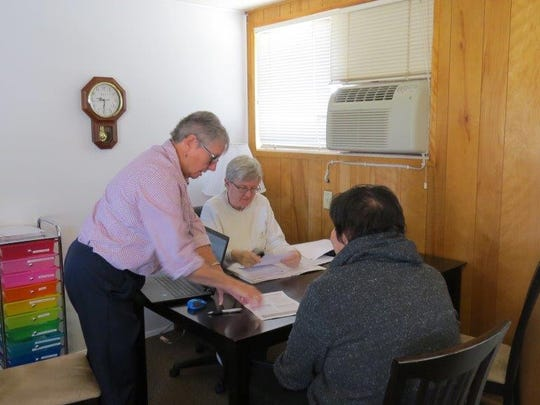 Sister Susan Kolb, a lawyer, seated in back, and Sister Christi Ann Laudolff, standing, work with a client on citizenship.