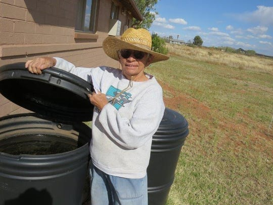 Sister Kathy Cook shows a rain barrel where water is collected in Naco, Ariz.