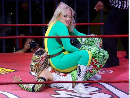 Lady Apache aplica una llave de escorpión a su rival.