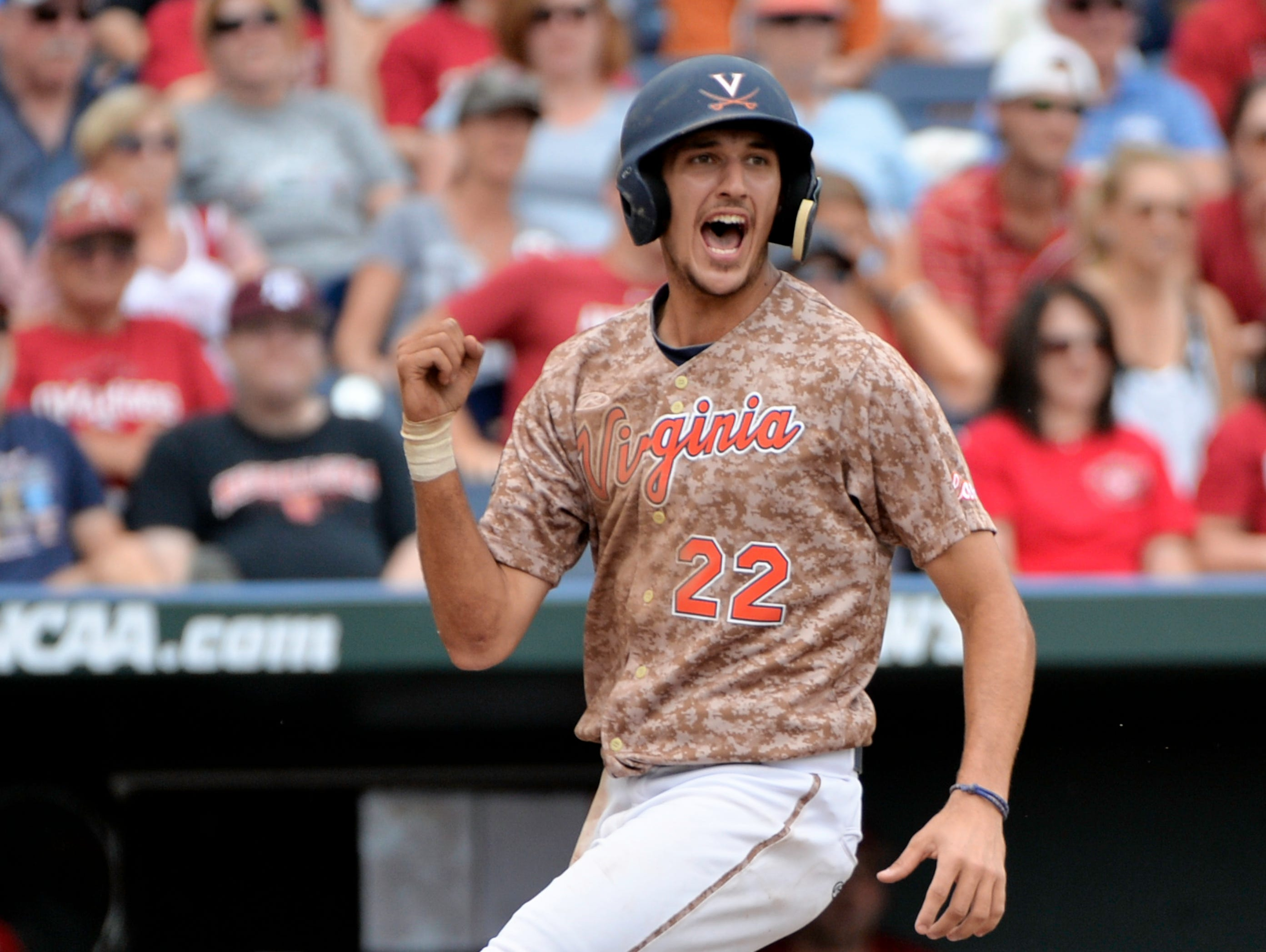 Virginia's Daniel Pinero celebrates after scoring on a RBI double by Kenny Towns in the eighth inning against Arkansas during the opening game of the College World Series at TD Ameritrade Park in Omaha, Neb. Virginia won 5-3.
