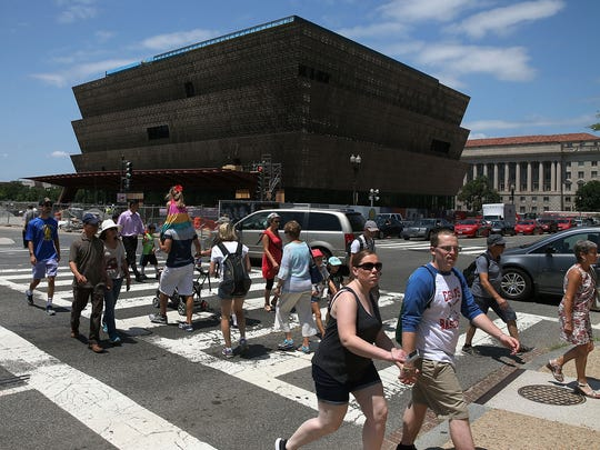Tourists walk past the Smithsonian Museum of African