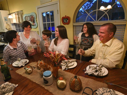 Ben (left), Aimee, Lucas, Kayla Ann, Aubrey and Clay have a glass of sparkling grape juice as a Thanksgiving family tradition.