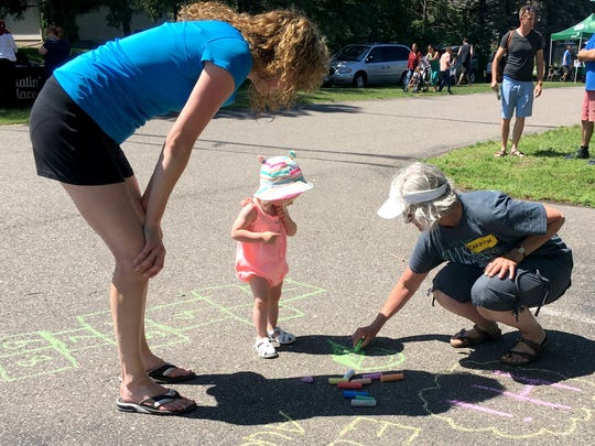 A Girls Scouts volunteer shows a little girl how to use sidewalk chalk. The group was part of a Girls Scouts Block Party in Waite Park Saturday, July 22, 2017.