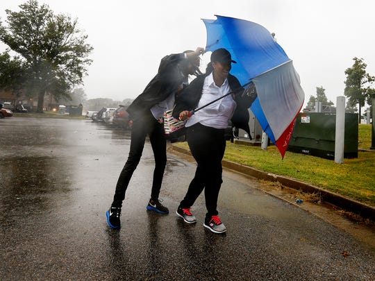 University of Memphis fans Deborah Rooks (right) along with daughter Alexis Rooks (left) battle the heavy rains and winds outside Liberty Bowl Memorial Stadium before the Tigers first football game of the season against Louisiana-Monroe, Thursday evening.