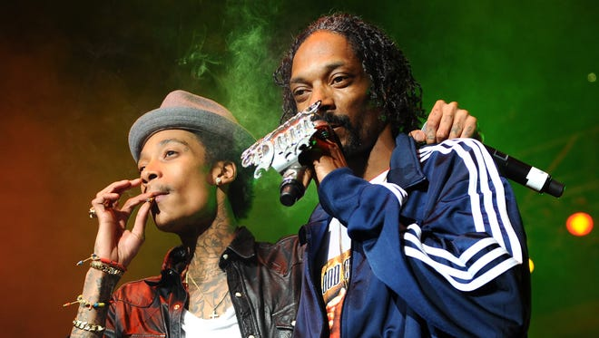 Wiz Khalifa (L) and Snoop Dogg perform on stage at Bankers Life Fieldhouse on February 2, 2012 in Indianapolis, Indiana.