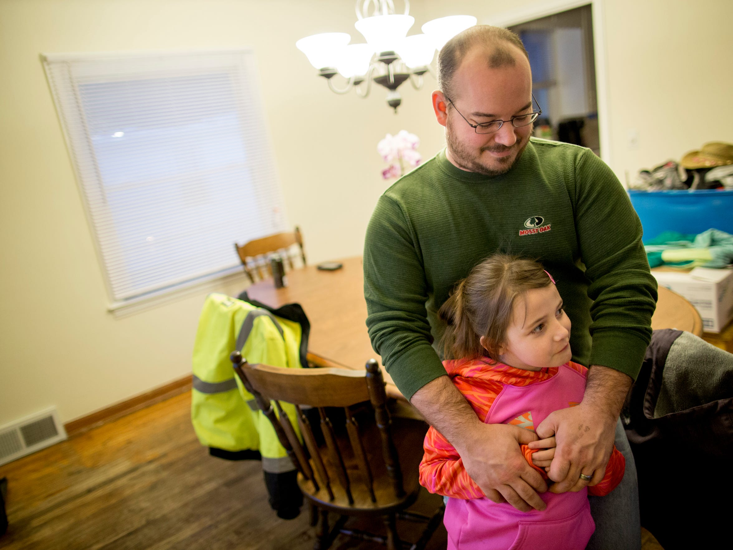 Kevin VanHamlin hugs his daughter Lauralee, 7, Saturday, Jan. 16, 2016, in the dinning room at their 24th Street home in Port Huron. The VanHamlin family had received a grant from the Urban Pioneer Program to purchase their home.