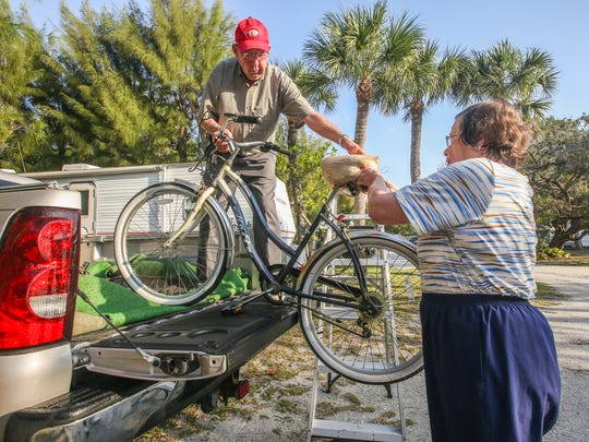 They load one of their bikes into the bed of their truck. Waylon and Barbara Snead have spent the entire month of March at Sanibel's Periwinkle Park campground for the past 19 years. They departed with their travel trailer Friday morning, for their home in Raleigh North Carolina. They spent Friday morning packing up the last few things into the back of their pickup truck and trailer for the four-day journey. They will stop and visit friends and family along the way home. Shot on April 1, 2016.