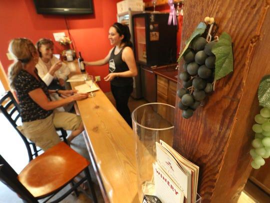 Gigi Smith, foreground and Audrey Ziegler taste wine